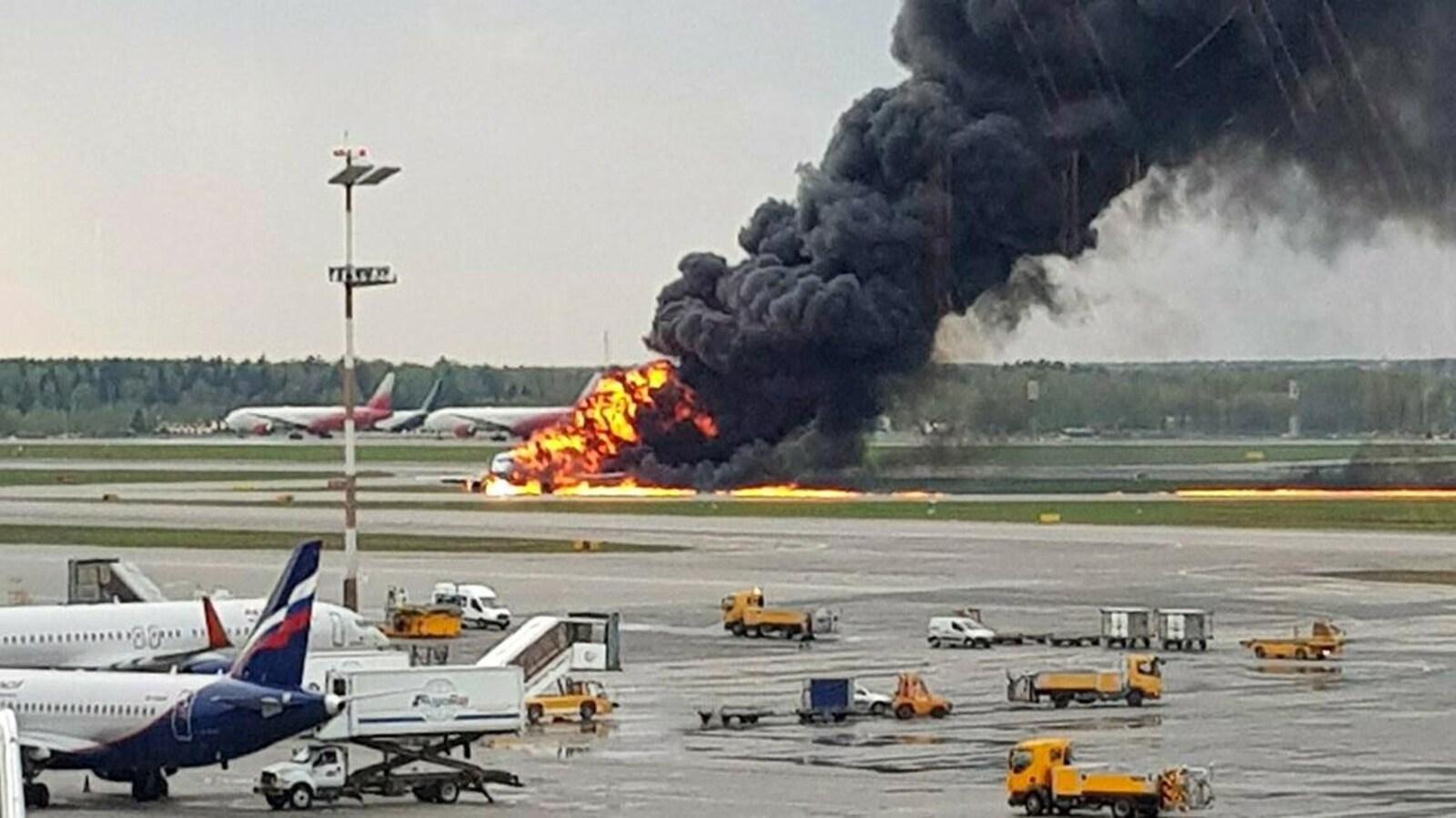 Un avion en flammes sur une piste d'un aéroport