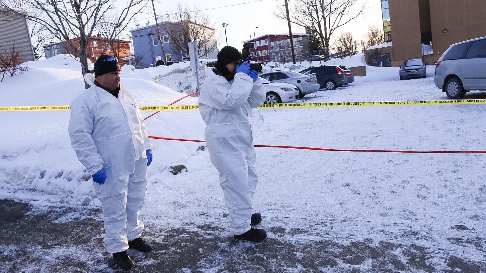 Des techniciens de la Sûreté du Québec, dans la neige, prenant des photos sur la scène de crime, à la mosquée de Québec.