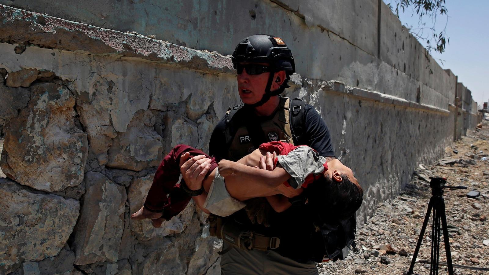 Un membre de la presse transporte un enfant gravement déshydraté dans un quartier de Mossoul.