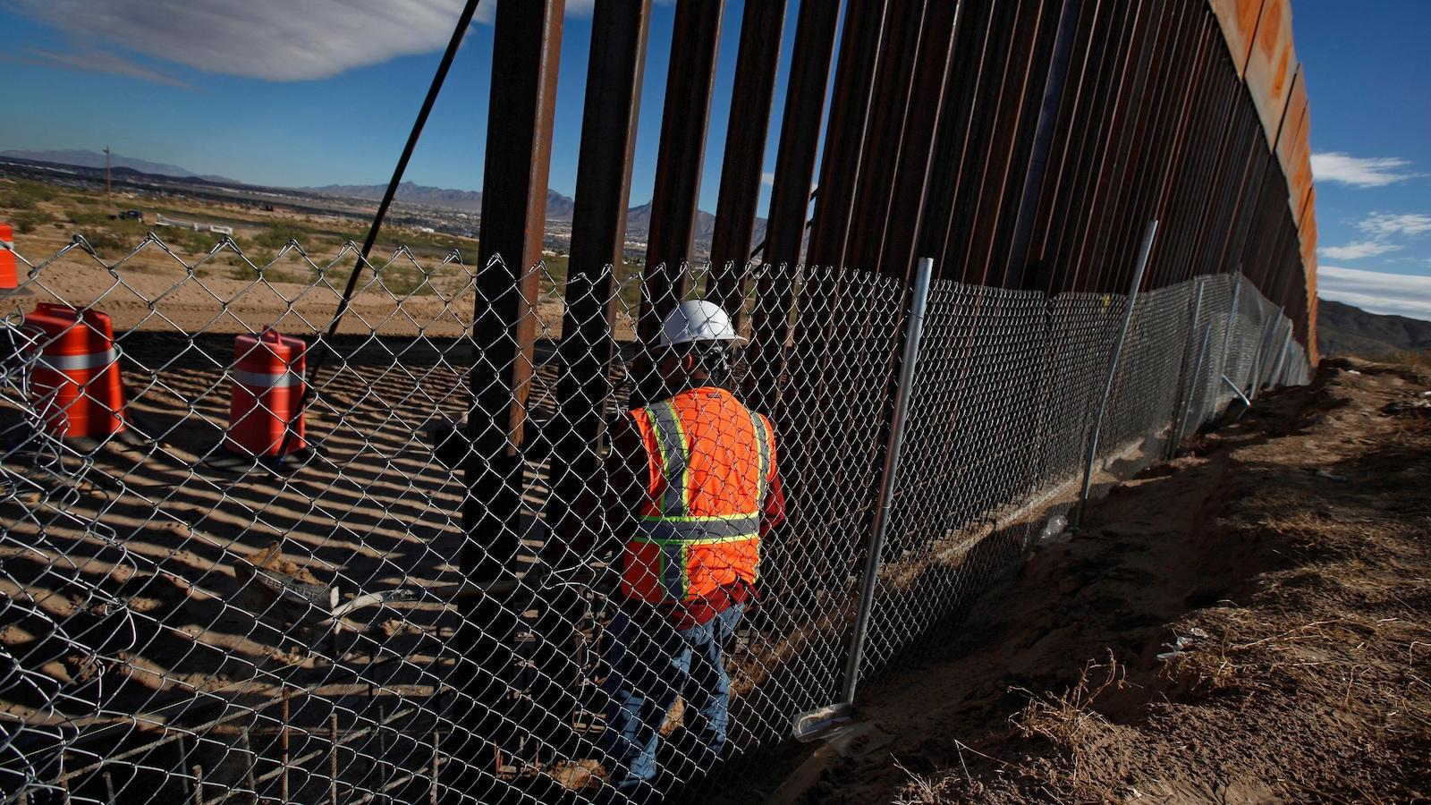 Un homme travaille à la construction d'un mur à la frontière entre les États-Unis et le Mexique.