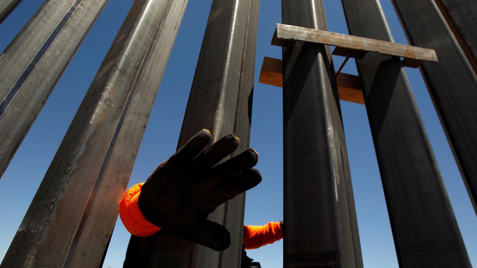 Un agent de sécurité privé bloque la caméra pour éviter d'être photographié sur une nouvelle section du mur de Santa Teresa, au Nouveau-Mexique, du côté mexicain de la frontière à San Jeronimo, à la périphérie de Ciudad Juarez, Mexique le 23 avril 2018