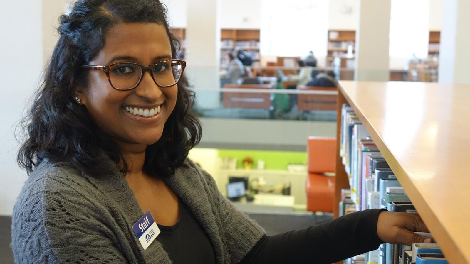 La bibliothécaire Nalini Battu range des livres dans les étagères.