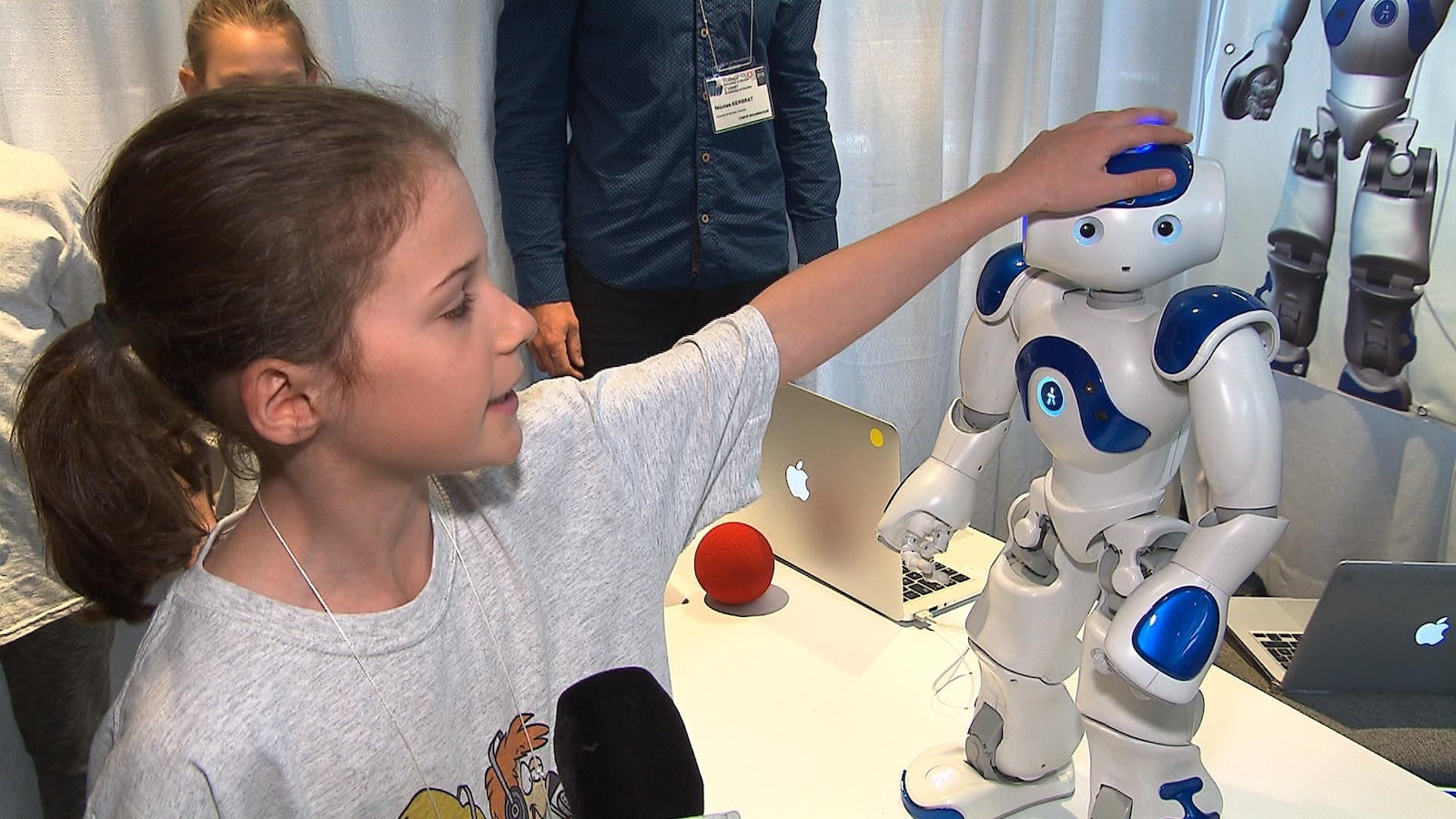 Une enfant caresse la tête du robot Nao