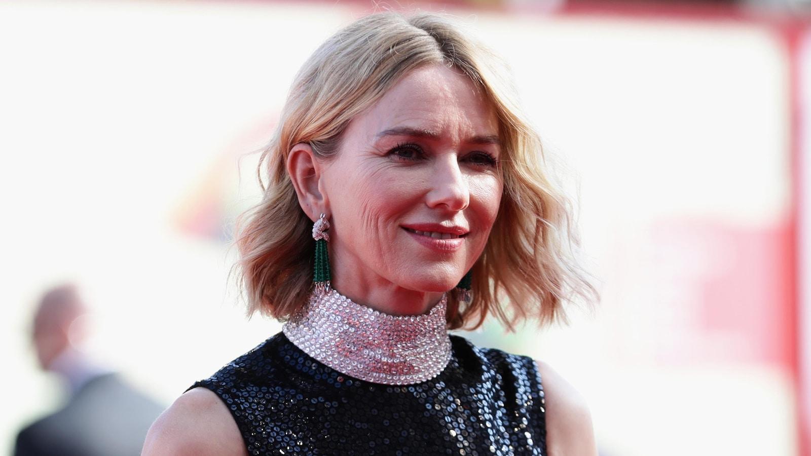 Naomi Watts en tenue de gala, souriante.