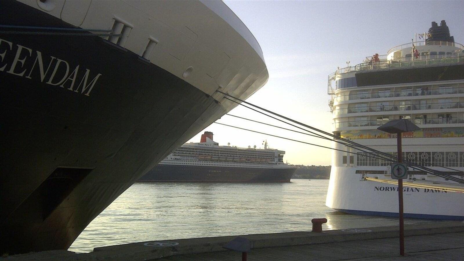 Deux navires de croisière amarrés au quai, dans le port de Québec, pendant que le navire Queen Mary 2 navigue, en retrait.