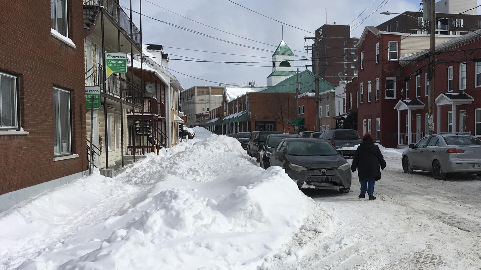 Une femme marche dans une rue de Trois-Rivières à côté d'un trottoir recouvert de neige.
