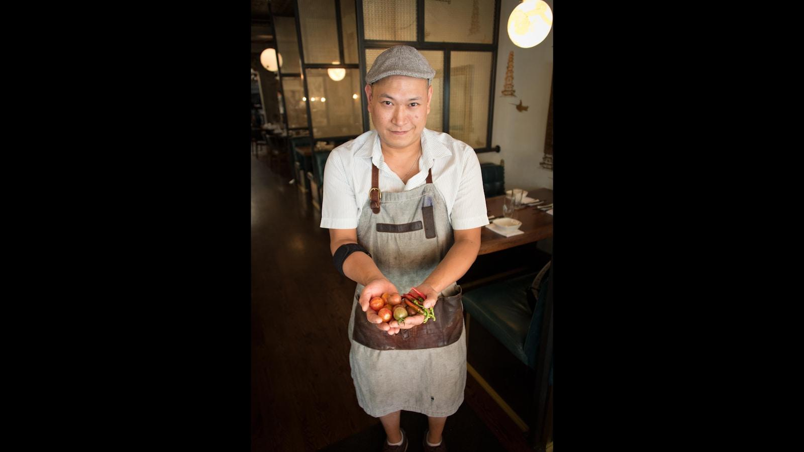 Un homme avec une casquette grise tient des légumes frais