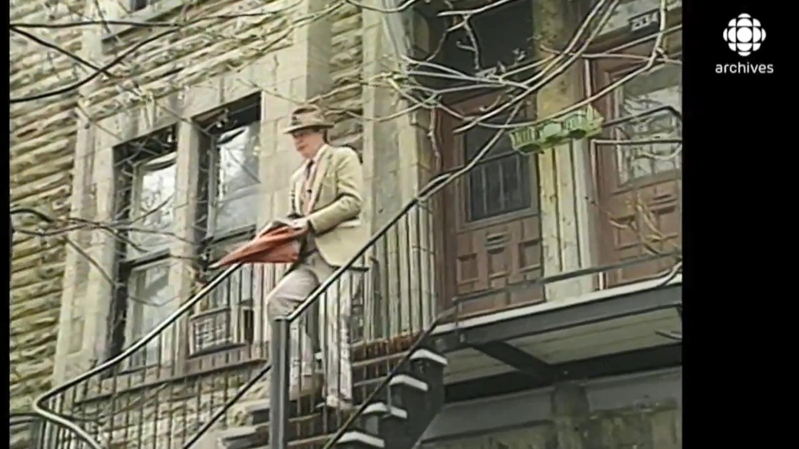 Nick Auf der Maur sort de son appartement chapeau sur la tête et parapluie à la main