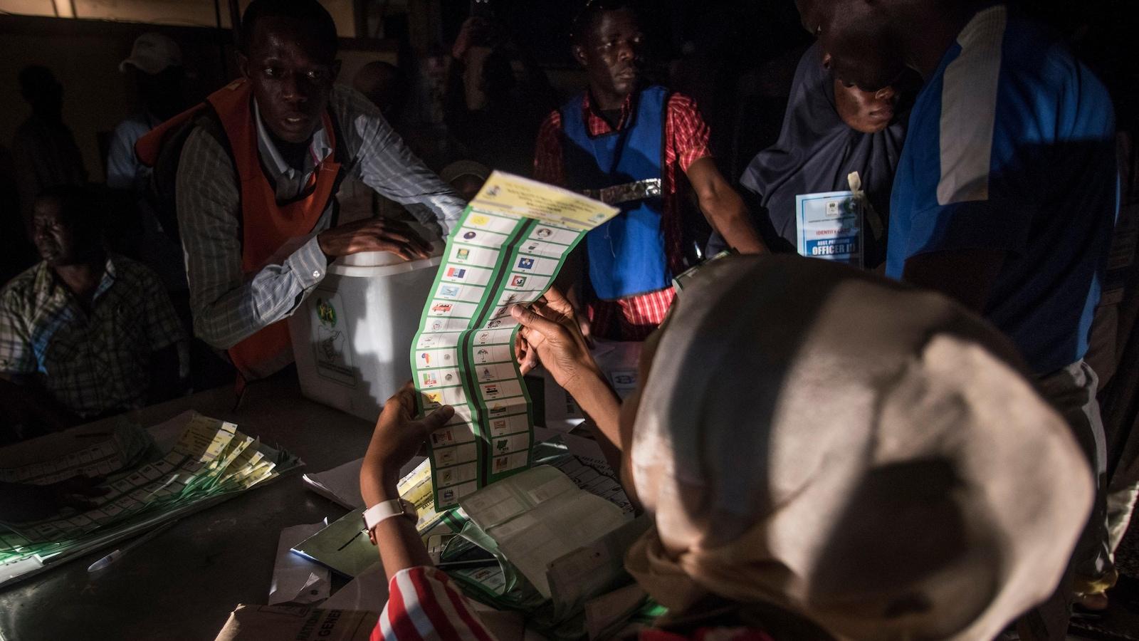 Une femme regarde un bulletin de vote alors que d'autres personnes s'affairent autour d'elle dans une pièce plongée dans la pénombre.
