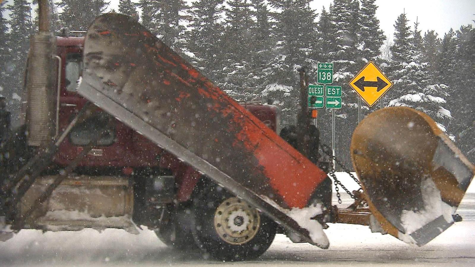 Un gros camion muni d'une niveleuse circule dans la neige sur la route 138