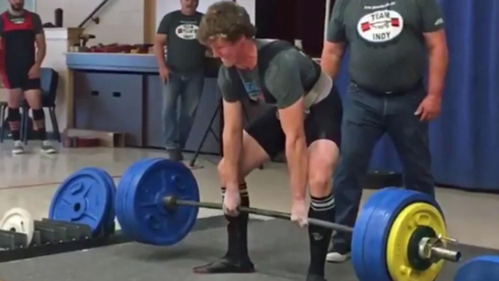 Noah Manning est en train de soulever une barre lourde soutenant des poids en position de soulevé de terre.
