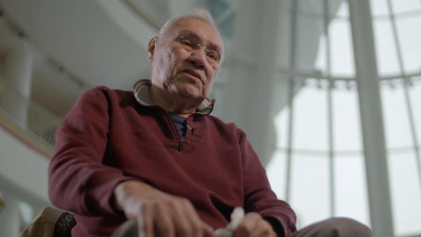 Un homme âgé est assis dans une salle avec beaucoup de fenêtres.