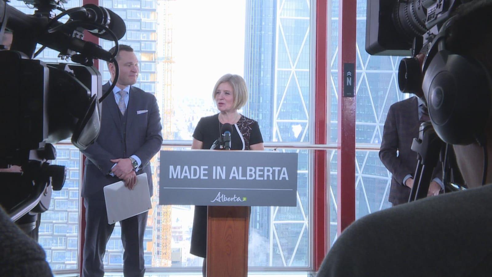 La première ministre Rachel Notley aux côtés du ministre du Développement économique et du Commerce de l'Alberta, Deron Bilous, devant des caméras au dernier étage de la Tour Calgary.