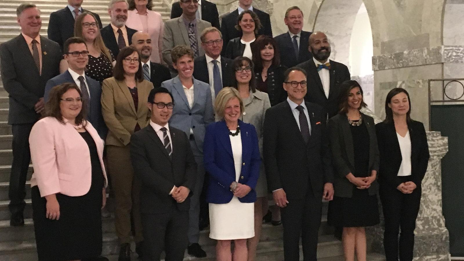 Tous les députés sont debout dans les marches de l'Assemblée législative. Rachel Notley est au milieu.
