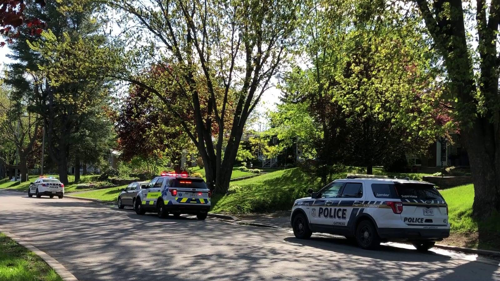 Des voitures de police et de premiers secours stationnées devant une résidence.