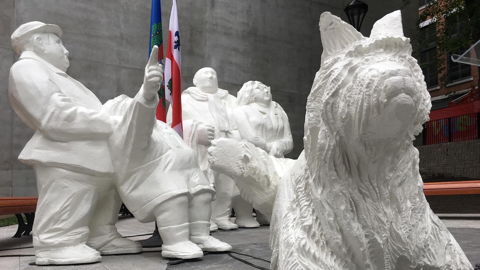 L'oeuvre Les touristes, d'Elisabeth Buffoli, dans le Jardin de Paris du parc de La Presse, à Montréal, montrant quatre personnages, dont un pointe vers le haut, et un chien.