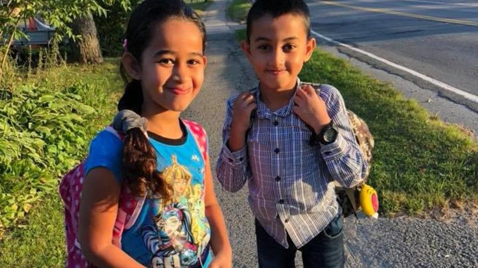 Les deux jeunes enfants de la famille Barho avec un sac à dos, sur le chemin de l'école.