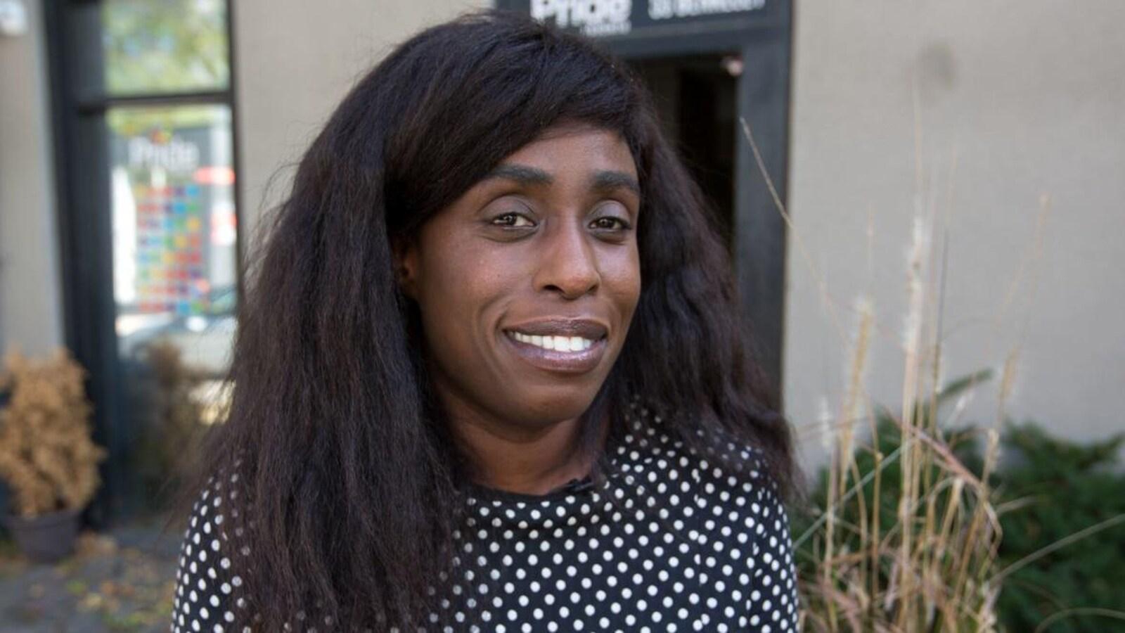 Photo d'une femme noire aux cheveux longs à l'extérieur d'un édifice