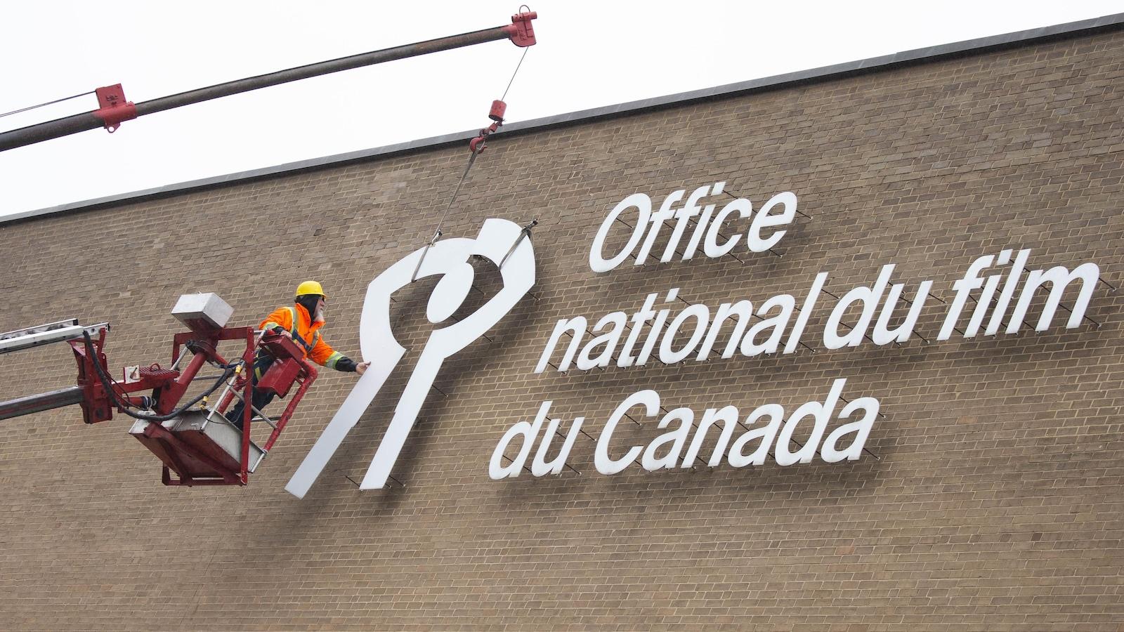Un travailleur retire le logo représentant l'Office national du film (ONF) de la façade de l'immeuble.