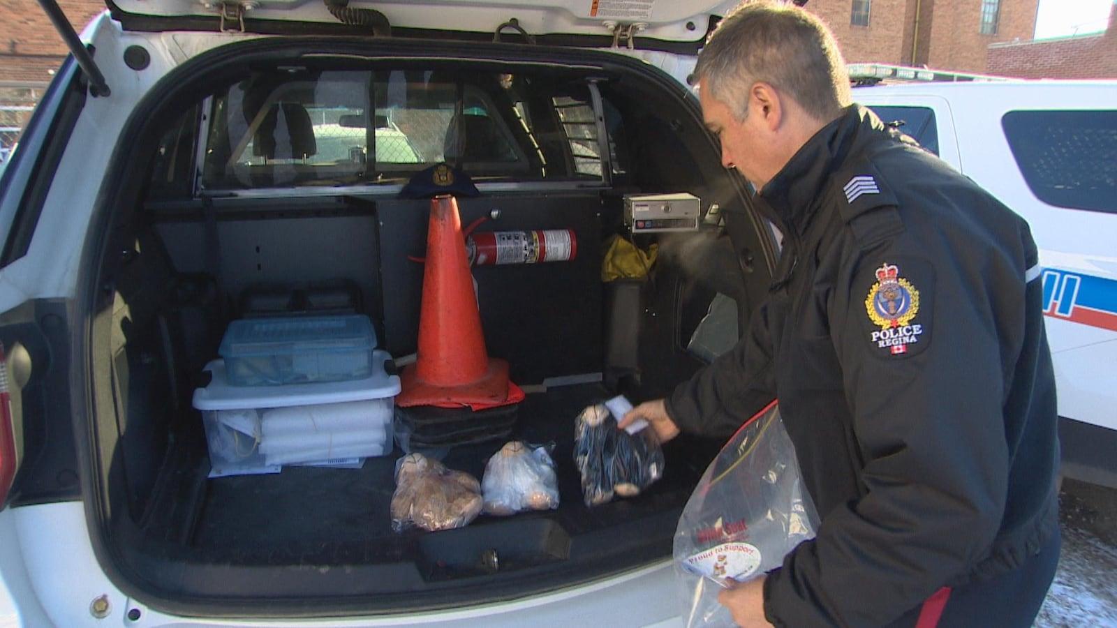 Un policier de Regina range des oursons en peluche dans sa voiture.