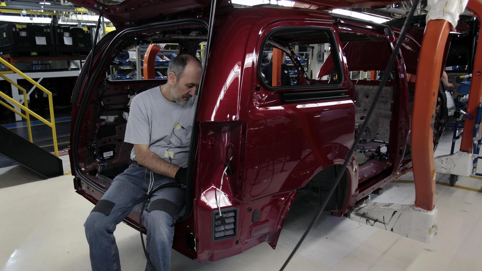 Un ouvrier assemble une Dodge Grand Caravan à l'usine de Chrysler à Windsor.