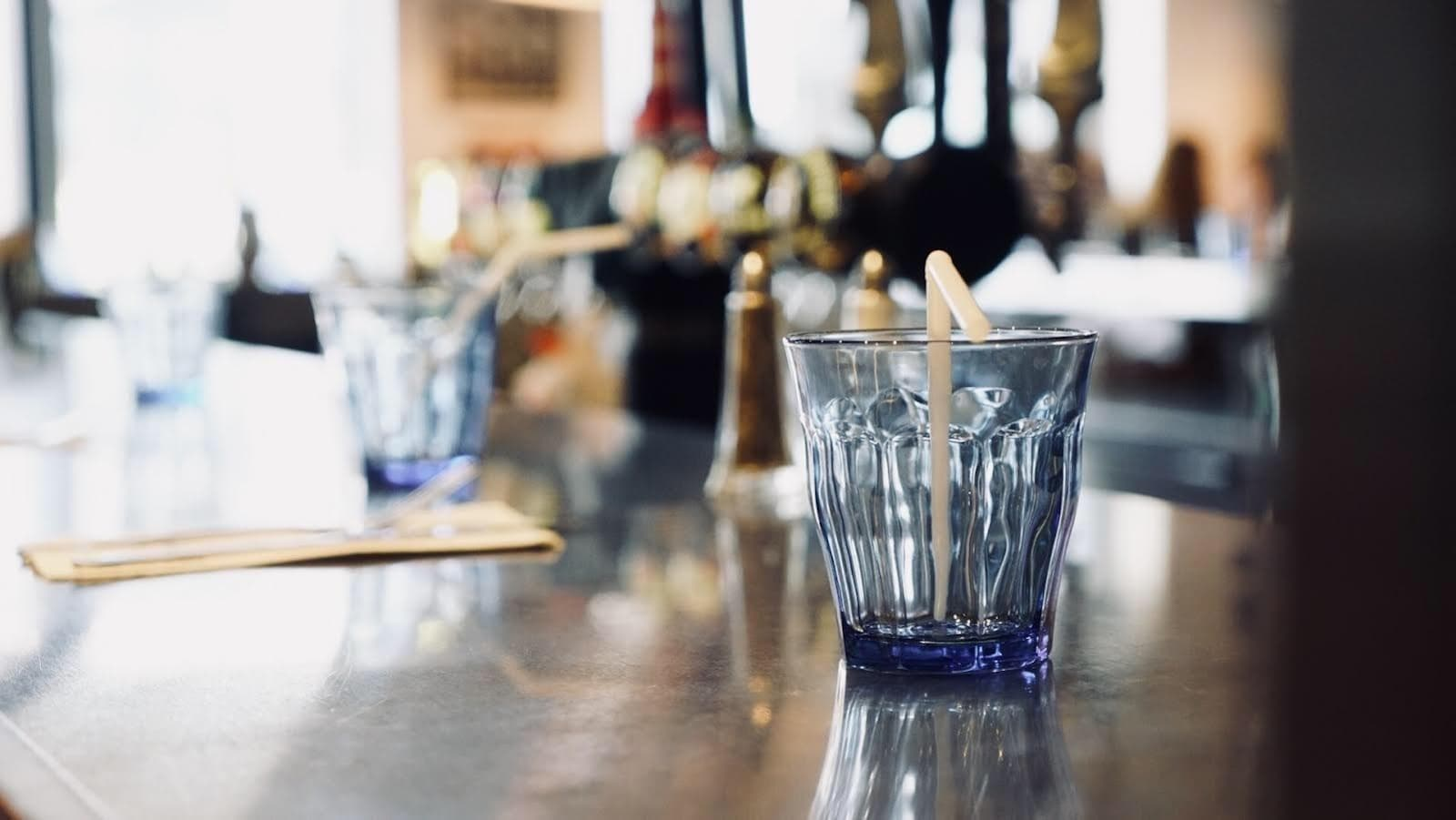 Un verre avec une paille de plastique sur le comptoir de restaurant