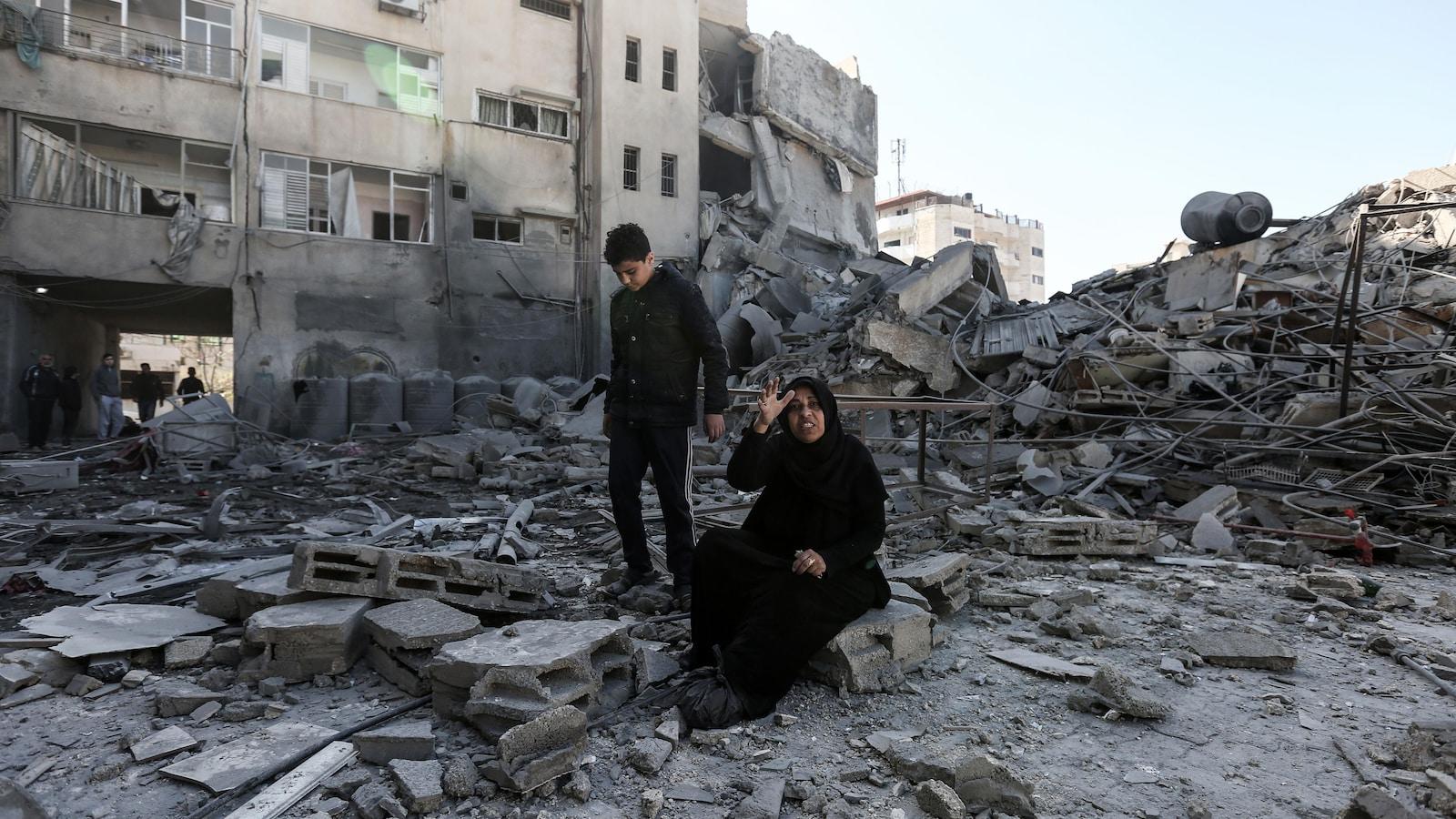 Une femme est assise sur des débris.