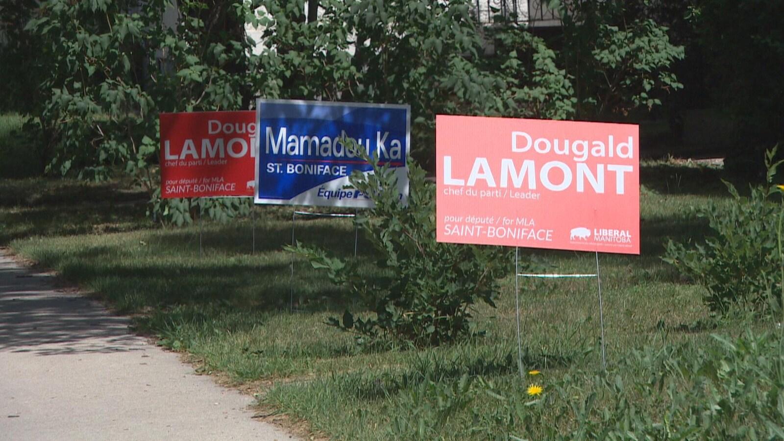 Deux pancartes rouges et une pancarte bleu sur une pelouse.