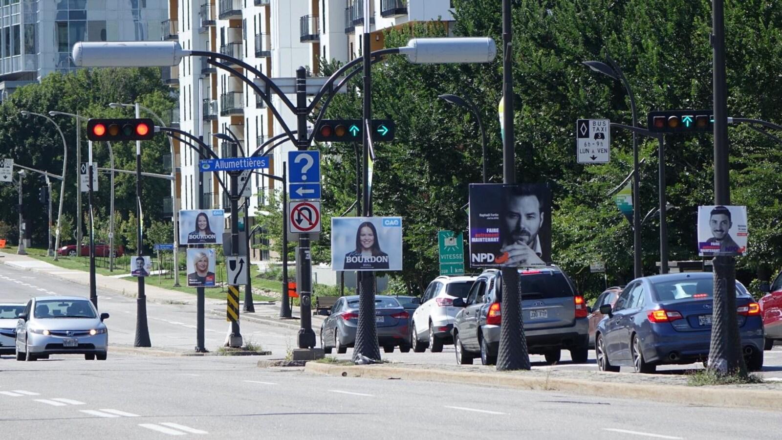 Des pancartes électorales sont accrochées à des poteaux. Des voitures circulent sur la route.