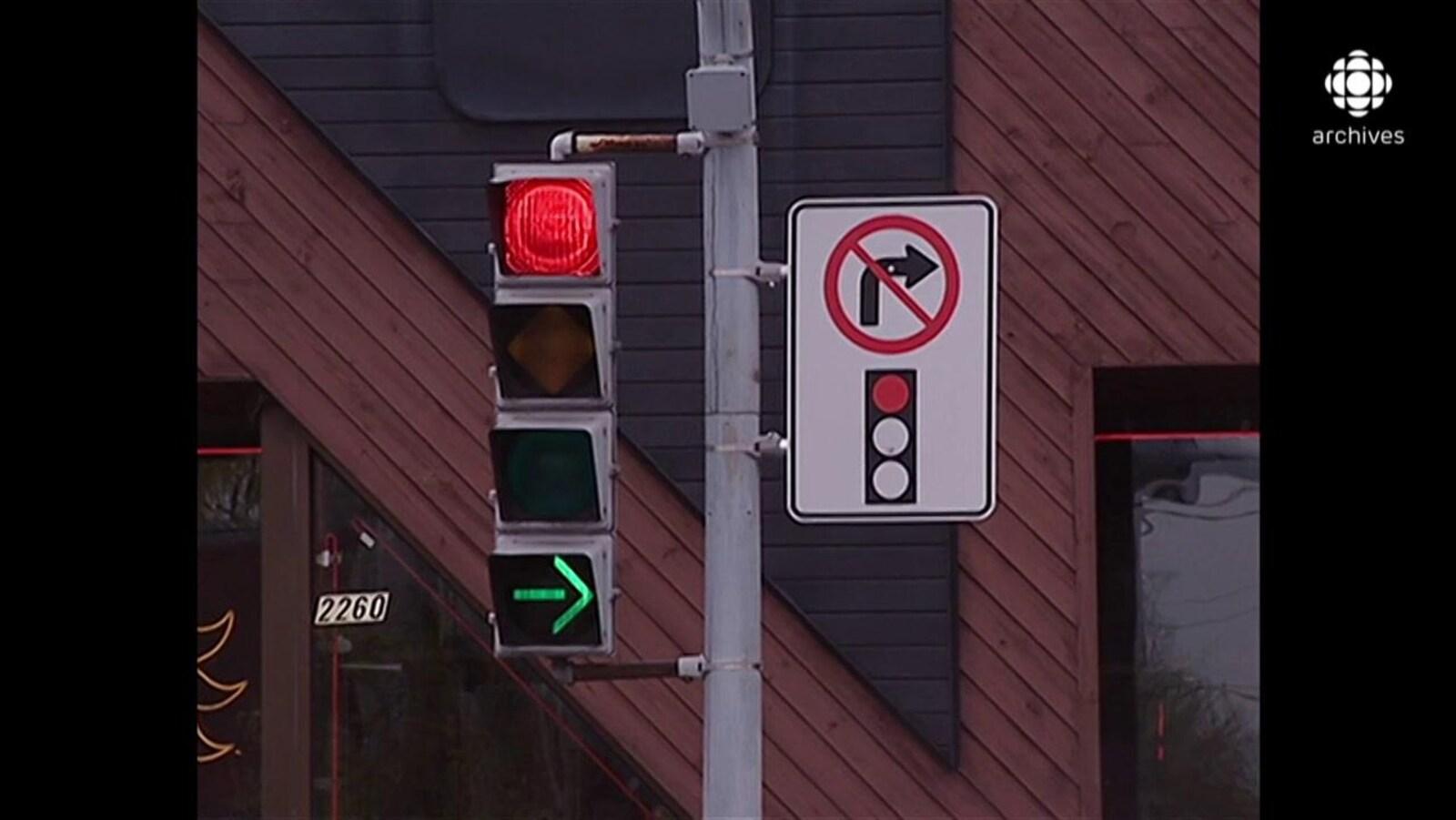 Panneau d'interdiction de virage à droite au feu rouge sur le même poteau qu'un feu de circulation indiquant un feu rouge, une flèche droite verte.