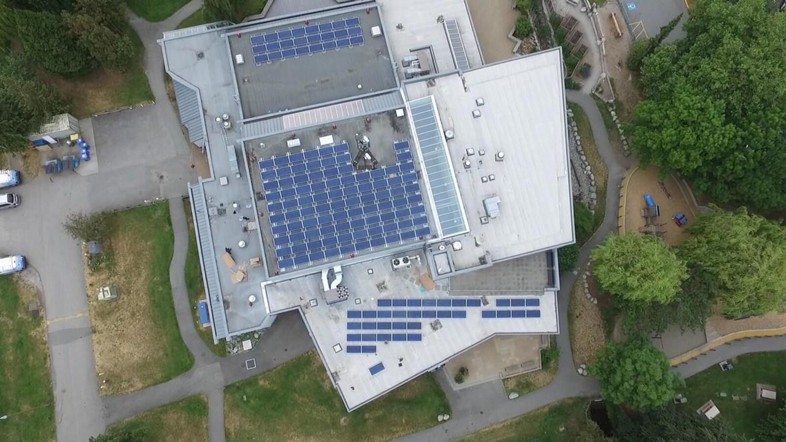 Vue aérienne du toit d'un bâtiment sur lequel sont installés plus d'une centaine de panneaux solaires.