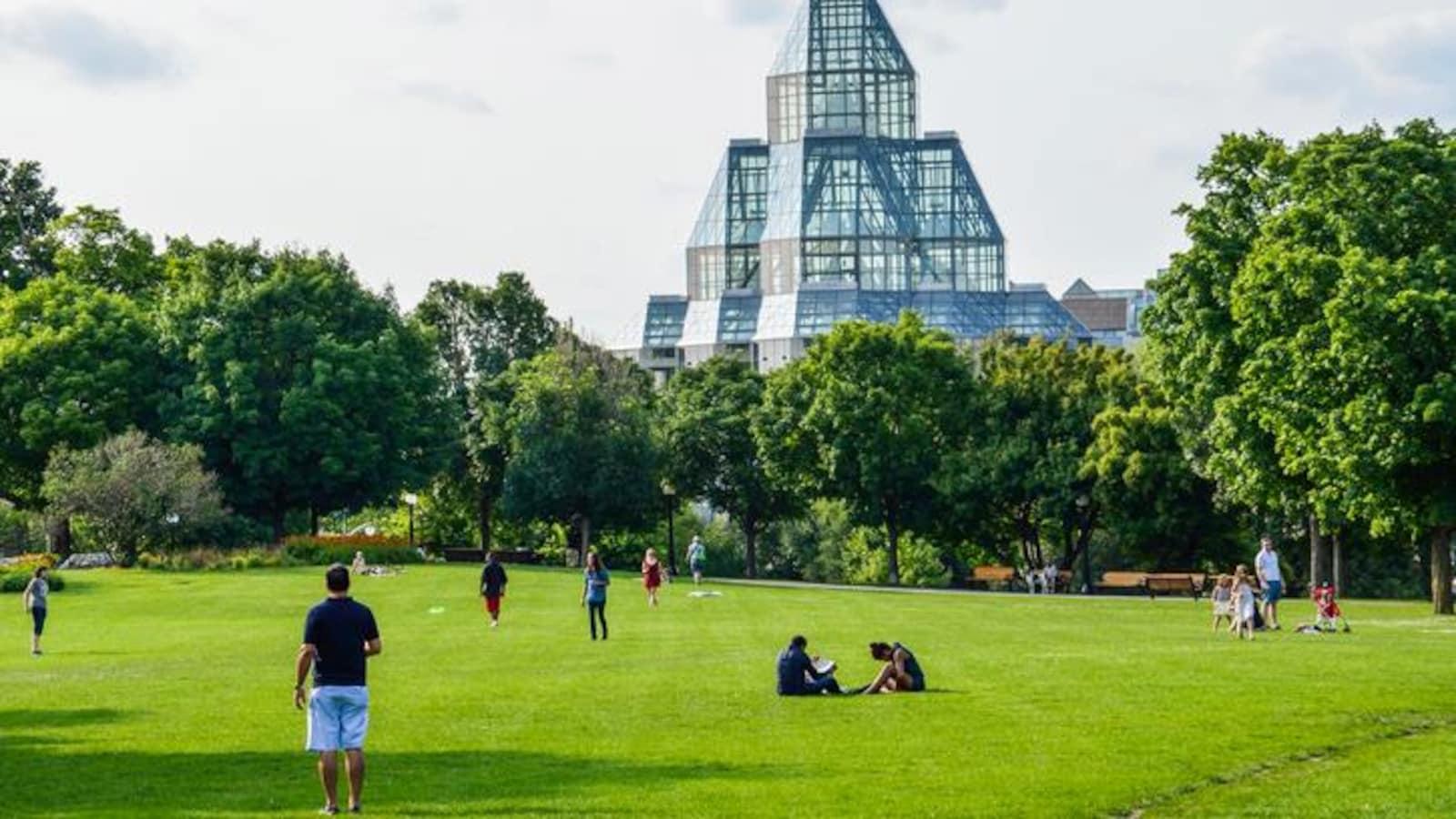 Des gens qui marchent et des gens qui sont assis sur le gazon devant le Musée des beaux-arts du Canada.