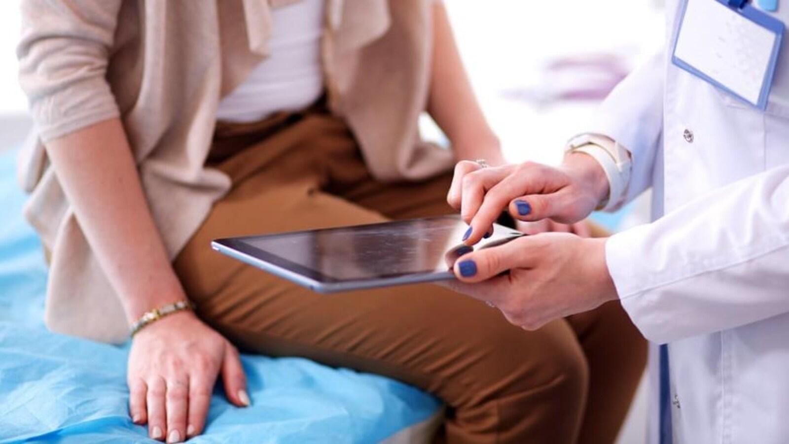 Une femme assise sur une table avec un professionnel de la santé qui tient un Ipad.