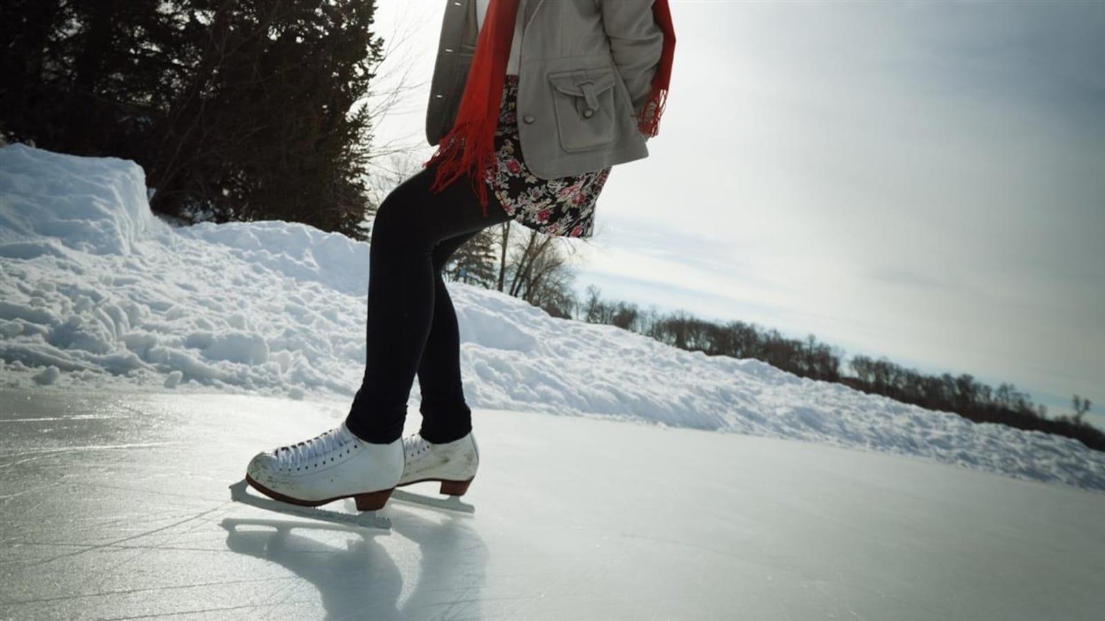 Une patineuse s'exerce sur un anneau de glace.