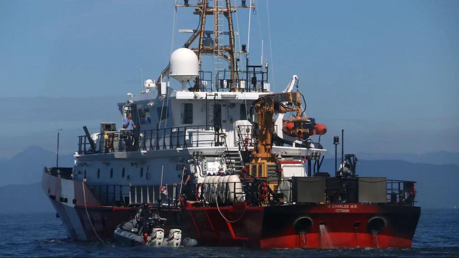 Un canot à coque gonflable rigide est amarré au navire de la Garde côtière sur une mer calme