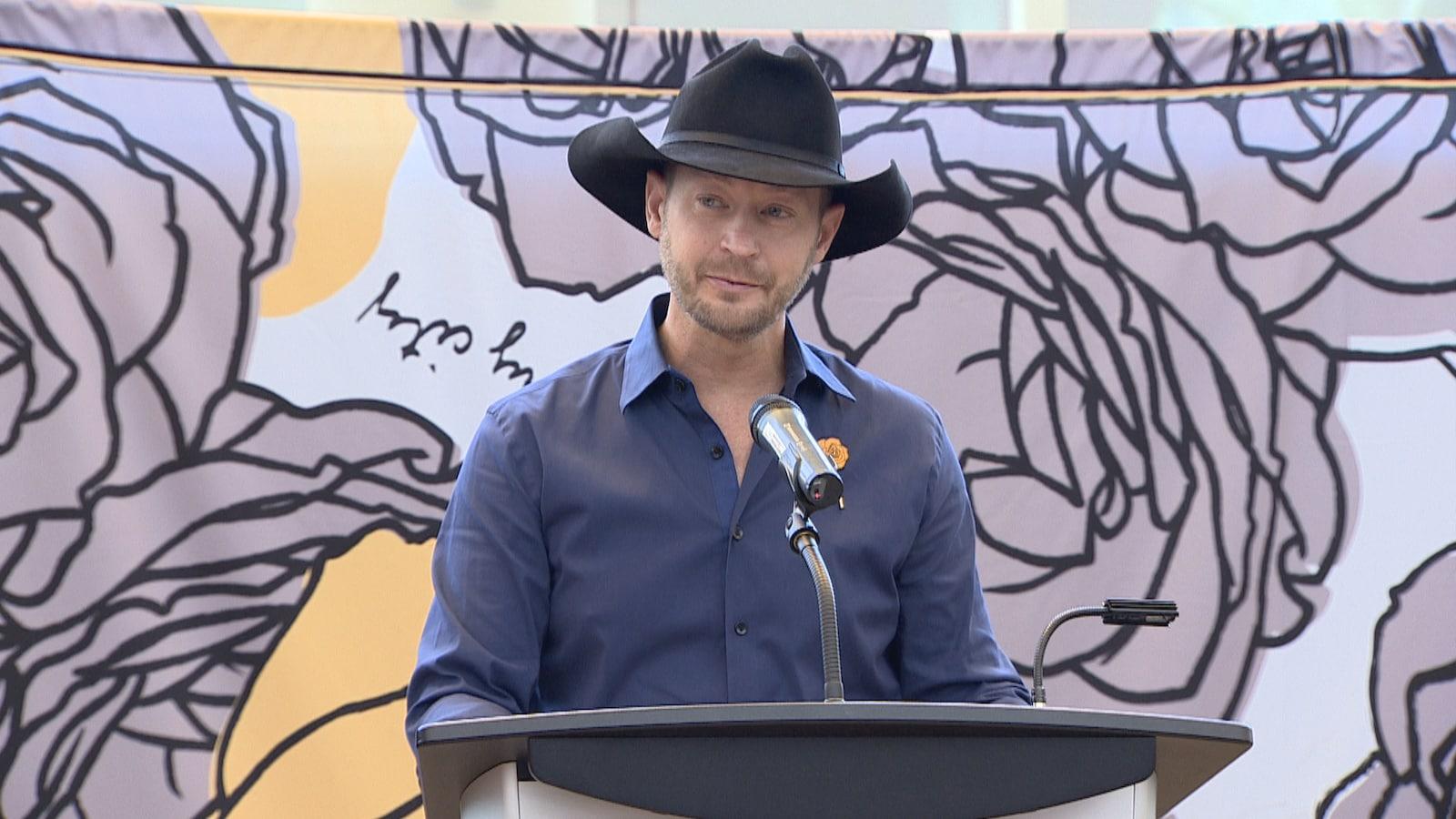 Le chanteur Paul Brandt fait une allocution devant une estrade avec micro. Derrière lui, une grande toile avec le logo de sa campagne de sensibilisation (des roses) est affichée.