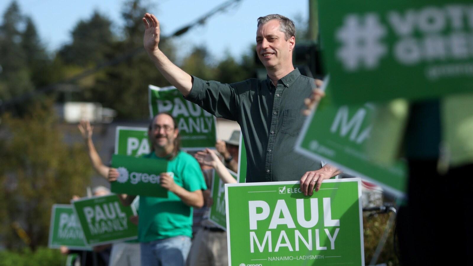 Paul Manly salue ses partisans lors d'un événement.