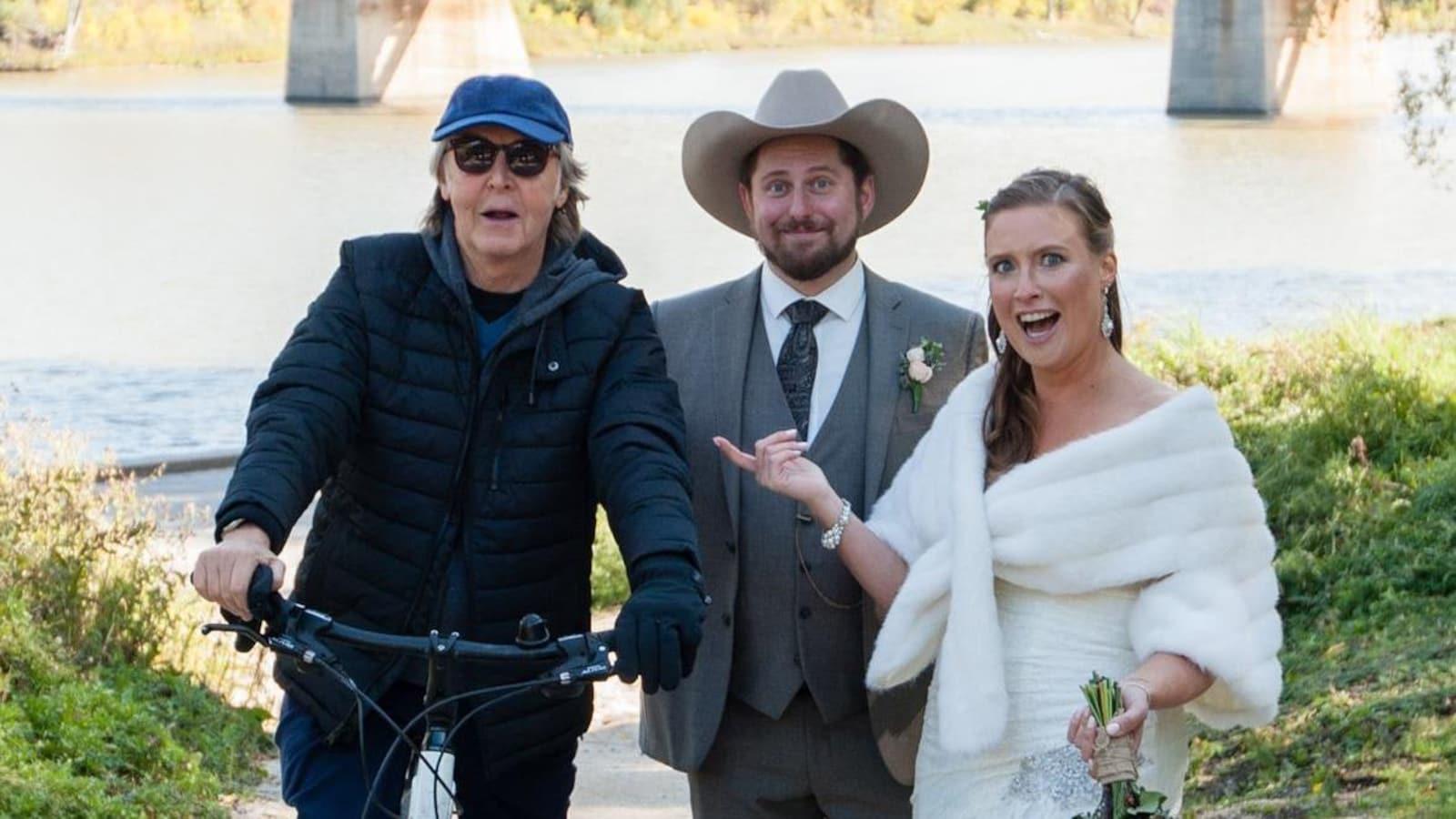 Un homme sur une bicyclette, un homme en habit avec un chapeau de cowboy et une femme en robe de mariée devant une rivière et un pont.