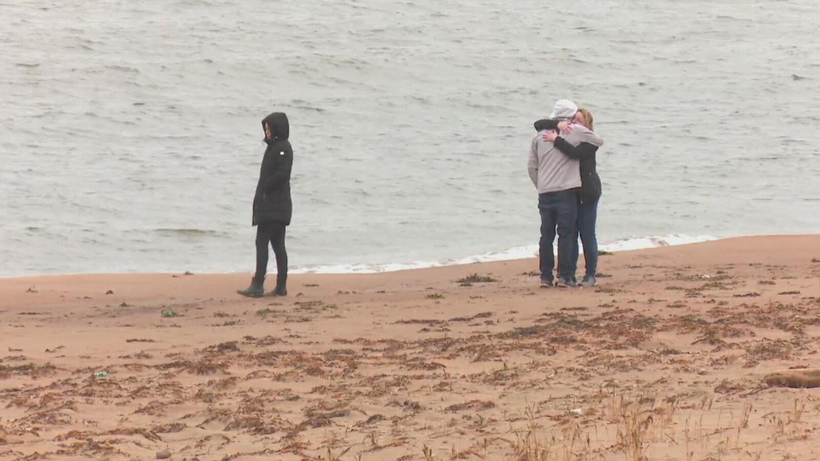Trois personnes sur la côte.