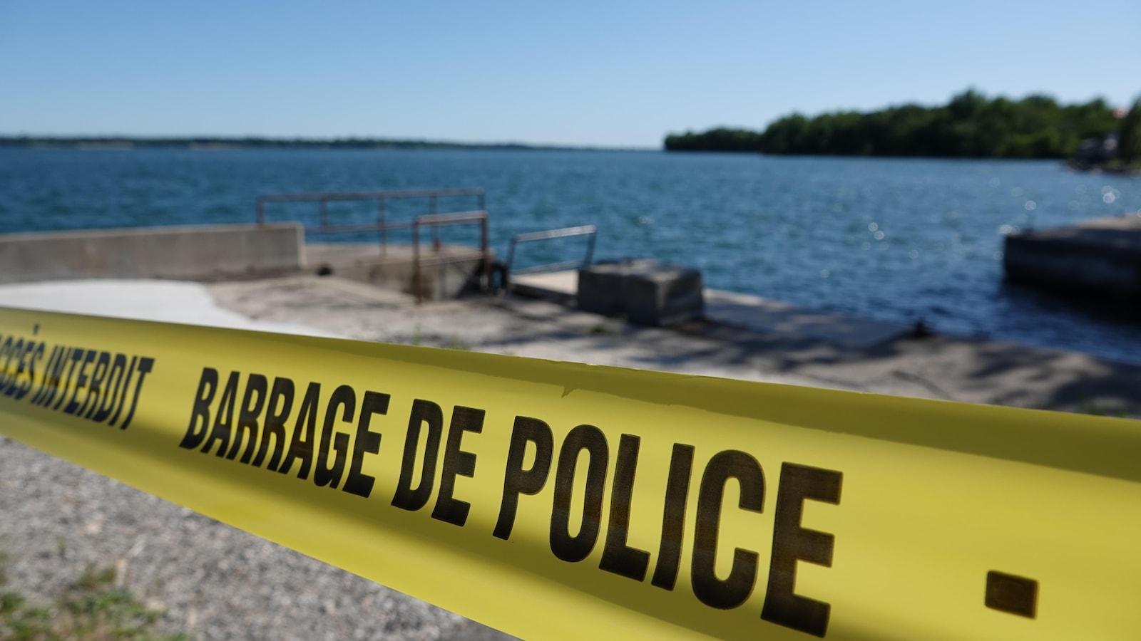 Un ruban sur lequel on peut lire « Barrage de police » est vu près d'une rive, lors d'une journée ensoleillée.
