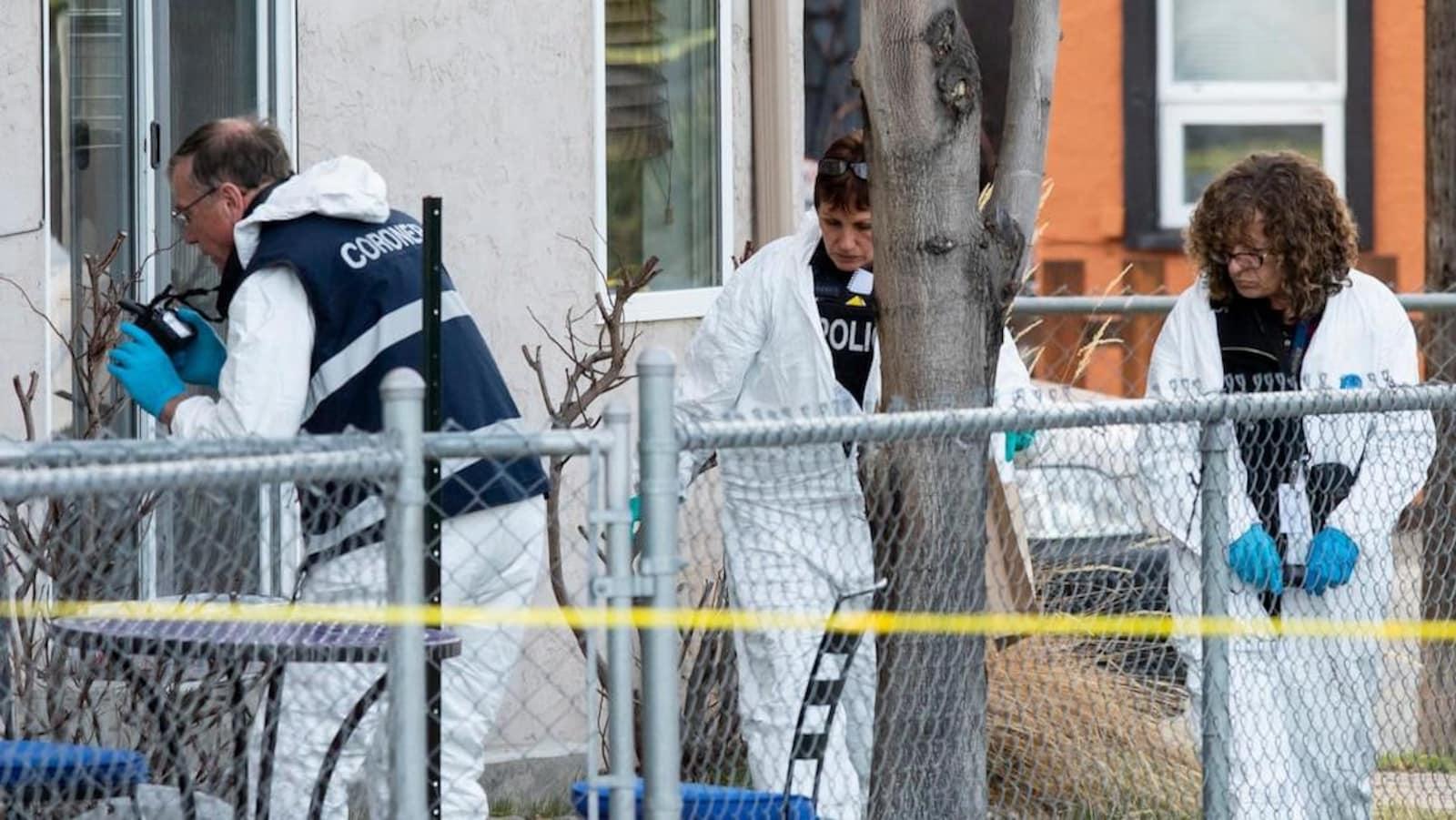 Trois agents travaillent dans une cour à ramasser des preuves.