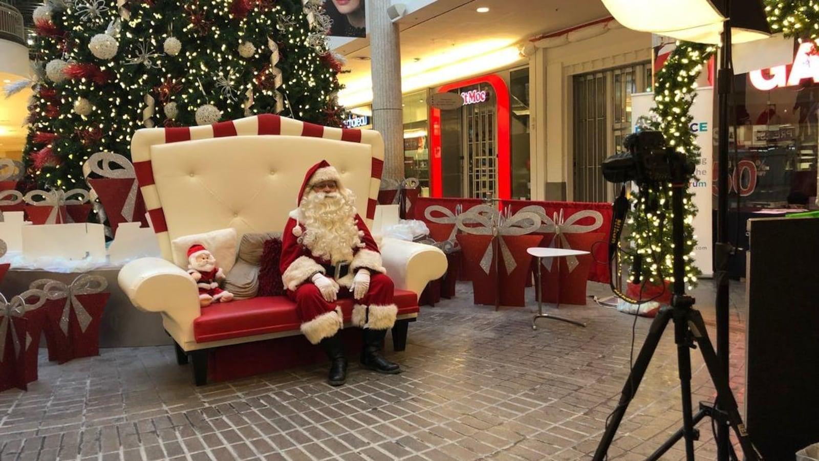 Le père Noël est assis sur un petit sofa de deux places, entouré d'un décor de Noël. Devant lui est installé une appareil photo.