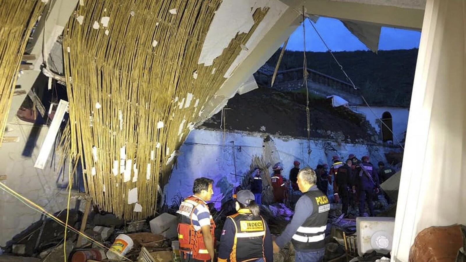 Des pompiers et des policiers péruviens observent les décombres d'un hôtel.