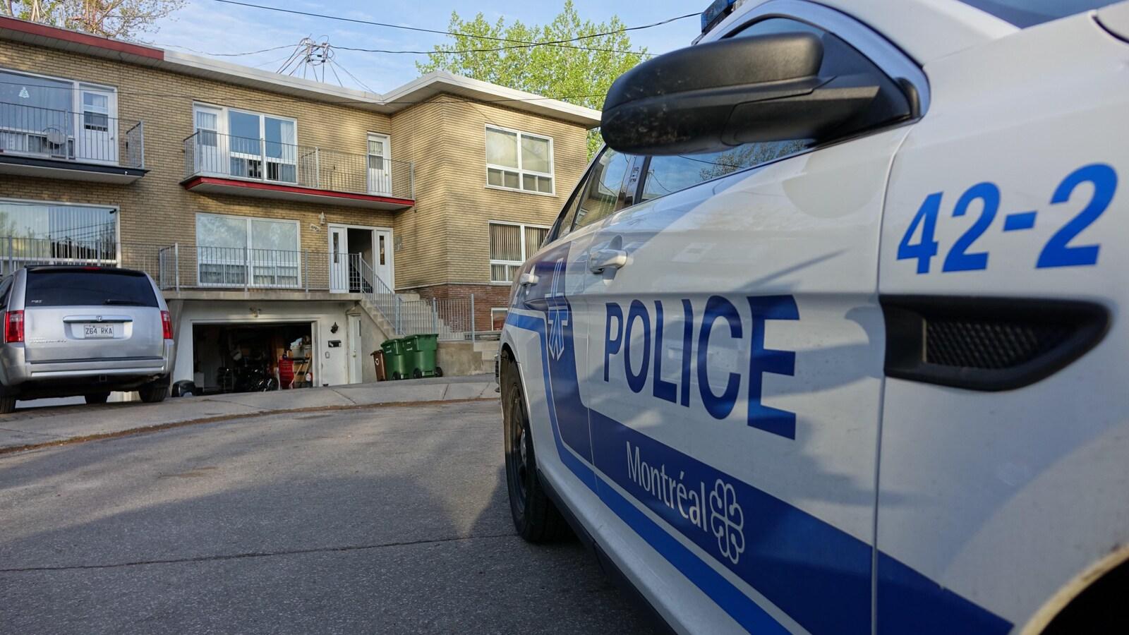 Une voiture de police devant le domicile d'un suspect