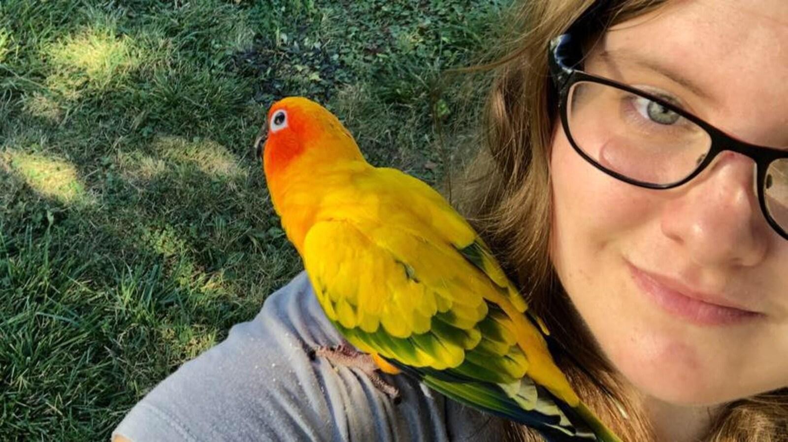 Une femme se prend en égoportrait avec un perroquet jaune sur son épaule.