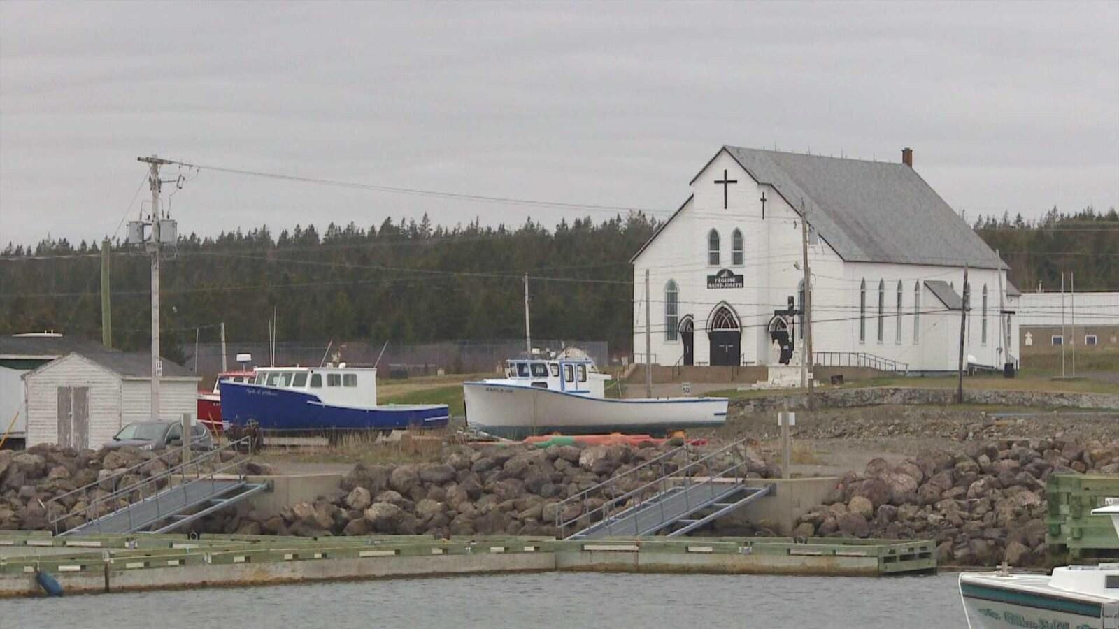Église et bateaux à Petit-de-Grat, en Nouvelle-Écosse.