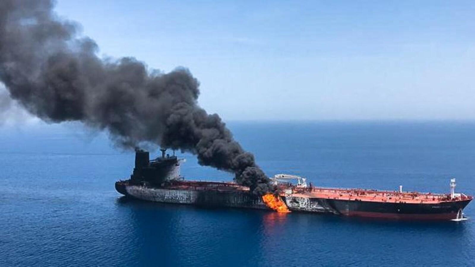 Des flammes et une colonne de fumée s'élèvent d'un pétrolier en mer.