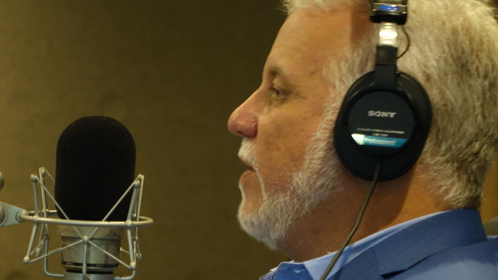 M. Couillard, écouteurs sur la tête, parle dans un micro, dans un studio de radio.