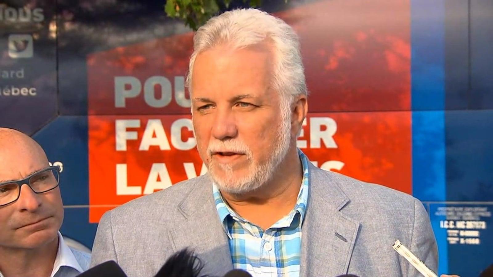 Philippe Couillard parle aux médias devant son autobus de campagne.