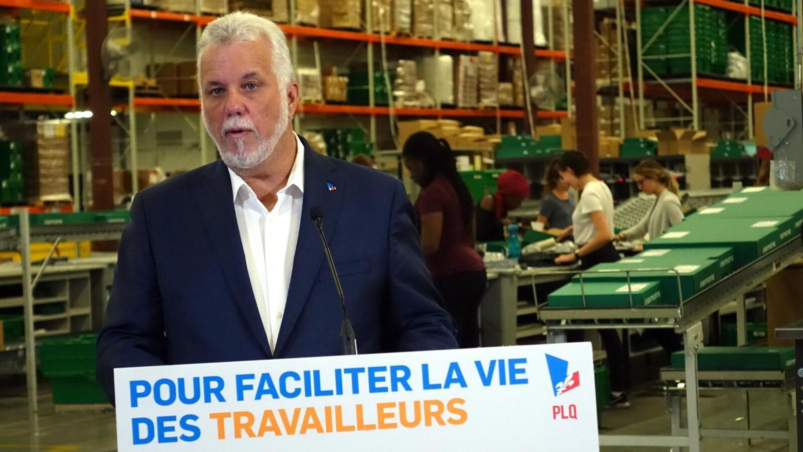 Philippe Couillard fait un point de presse dans le centre de distribution d'un magasin Simons. Des femmes travaillent derrière lui.